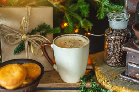 A mug of cappuccino coffee on a wooden background with green branches of a Christmas tree. Warm and cozy from a hot drink on Christmas morning.