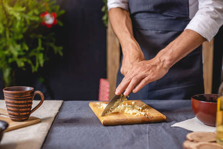 A male chef in a black apron prepares a Christmas dish by slicing garlic on a chopping Board. Joyful cooking for festive new year and Christmas table Banco de Imagens