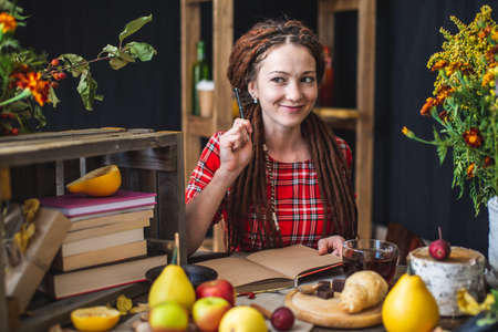 A beautiful young woman in a red dress sitting at an autumn table with yellow flowers and pumpkins is writing in a notebook. The concept of autumn romantic mood