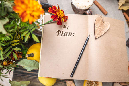Autumn set of yellow leaves and flowers. Notebook with open pages on the table. Space for text. Top view. Concept my plan