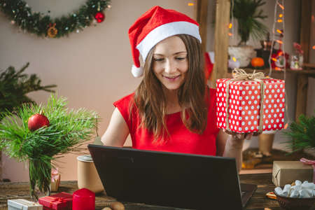 A beautiful woman in a red dress is holding a gift box and ordering online purchases on her laptop. Online shopping for Christmas holidays.