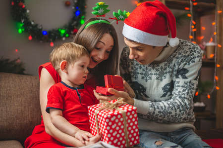 Mother and father give their son a gift in a red box. Young family with a child celebrates Christmas and New year in a cozy home environment