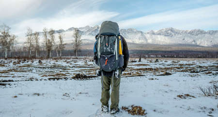 A man hiker with a large backpack stands with his back looking at the snowy mountains ahead. Concept the beginning of the path to achieving the goal