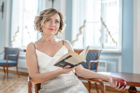 A beautiful woman in a white dress reading a book sitting on a sofa in a room in a classic blue interior. Bright sunlight shines from the window
