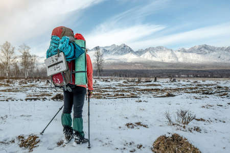 A woman hiker with a large backpack stands with his back looking at the snowy mountains ahead. Concept the beginning of the path to achieving the goal