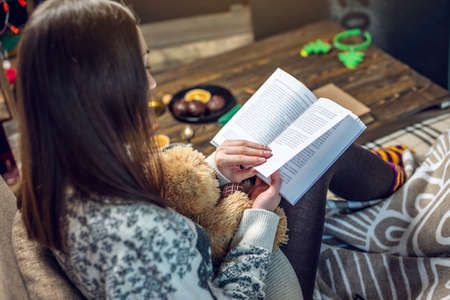 Young woman in a sweater reading a book with a mug of coffee in the evening in a warm Christmas atmosphere. Cozy new year mood