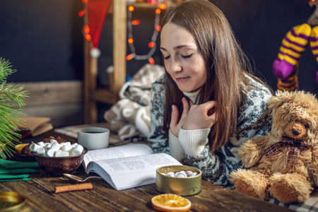 Young girl in a sweater reading a book with a mug of tea in the evening in a warm Christmas atmosphere. Cozy new year mood Stockfoto