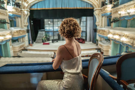 A beautiful woman in a dress alone on the balcony of a classical empty theater looks at the stage and interior