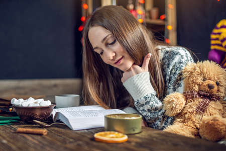 Young girl in a sweater reading a book with cup of coffee in the evening in a warm Christmas atmosphere. Cozy new year mood