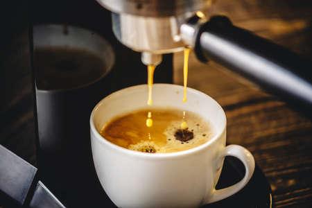 Espresso strömt aus der Kaffeemaschine in eine weiße Tasse und bildet einen goldenen Schaum Standard-Bild