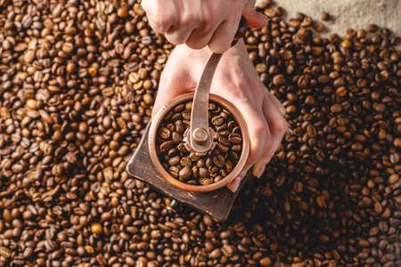 Hände, die auf einer manuellen Mühle duftende Kaffeebohnen mahlen. Ein Haufen gerösteter Arabica-Körner. Ansicht von oben. Auswahl an frischem Kaffee für Espresso Standard-Bild