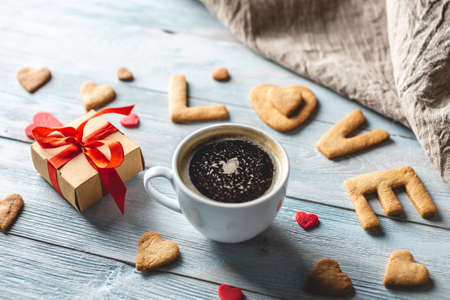 Cup of coffee and a message from a sweet cookie in the form of the word love on a blue wooden background. Romantic Valentines day gift 스톡 콘텐츠