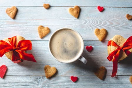 Cup of coffee and a sweet gift of cookies tied with red ribbon in the form of hearts on a blue wooden background. Romantic Valentines day gift 스톡 콘텐츠