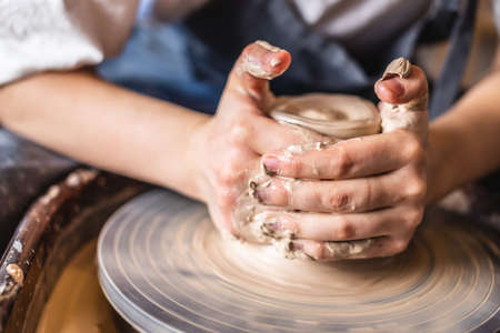 Potter working on a Potter's wheel making a vase. Young woman forming the clay with her hands creating jug in a workshop. Close up Stockfoto