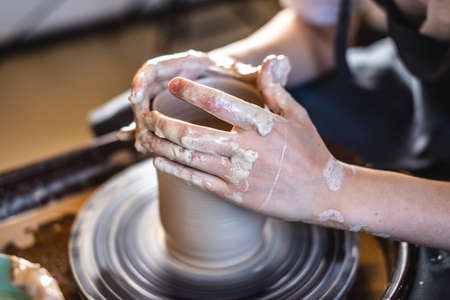 Potter working on a Potter's wheel making a vase. Woman forming the clay with her hands creating jug in a workshop. Close up Stockfoto