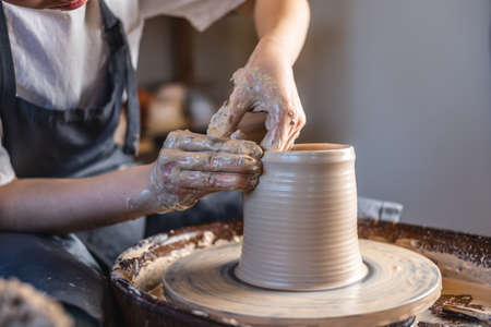 Potter working on a Potter's wheel making a vase. Young woman forming the clay with her hands creating jug in a workshop. Close up Stock fotó