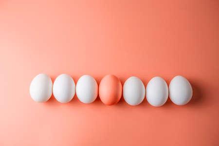 Uovo di Pasqua rosso brillante tra quelli bianchi su sfondo pastello. Biglietto di auguri per le feste di primavera
