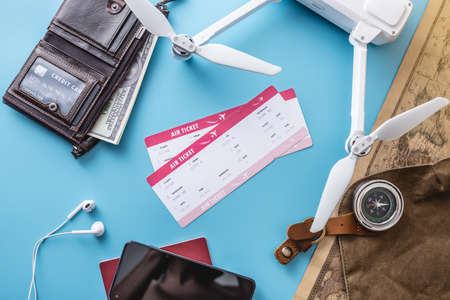Necessary things for the flight on vacation. Plane tickets, passport, cradit card, phone, drone quadcopter, camera, world map on a blue background. Concept of easy preparation for travel. Top view