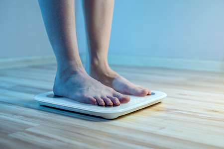 Women's bare feet stand on the floor electronic scales, to check the weight of the body and control the set of extra pounds in the blue light Stock Photo - 143046171