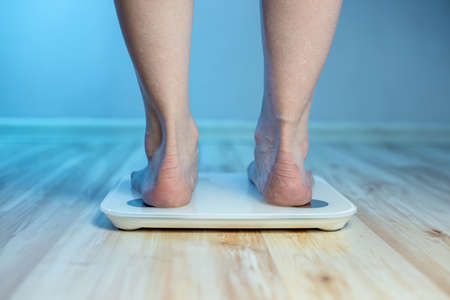 Womens bare feet stand on the floor electronic scales, to check the weight of the body and control the set of extra pounds in the blue light