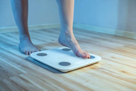 Women's bare feet stand on the floor electronic scales, to check the weight of the body and control the set of extra pounds in the blue light Stock Photo - 143058187