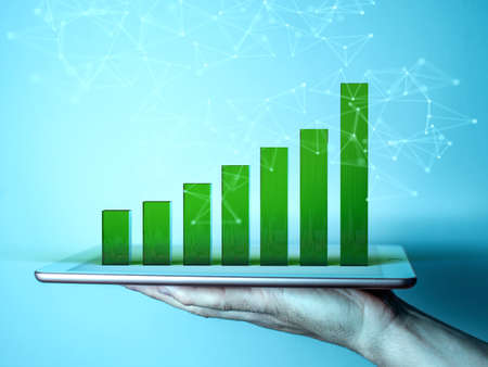 A man's hand holding a tablet. The screen of the gadget shows a 3d graph in the form of green columns illustrating growth