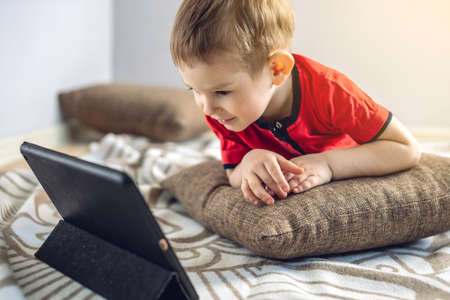 A happy preschool toddler child watches cartoons on a tablet on the internet. Gadgets and modern entertainment for children.