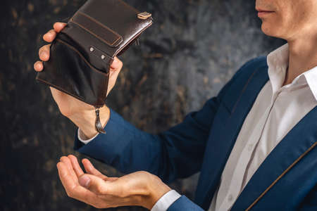 The man is holding an open empty brown leather wallet purse. The concept of economic crisis and business bankruptcy in the post-pandemic period Imagens