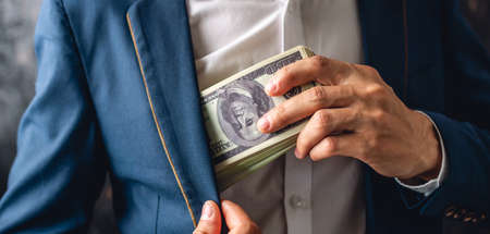 Man in a suit putting a wad of hundred-dollar bills in the inside pocket of his jacket. Close up. The concept of corruption and bribery officials Фото со стока