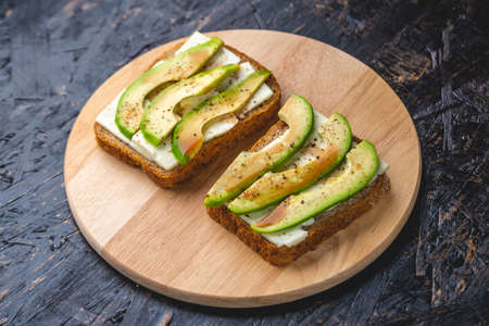 Healthy vegetarian sandwiches with sliced avocado and tofu cheese. Modern and simple Breakfast for every day