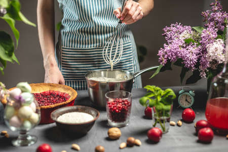 Cooking homemade cranberry pie. A female pastry chef is whipping up a whisk of sour cream. Table with bright ingredients in spring style with flowers