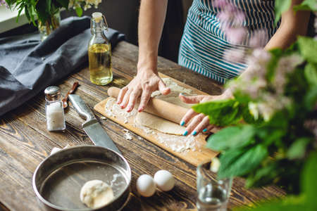 The woman is rolling out fresh dough for making pasta in a cozy atmosphere. Concept of cooking tasty food at home