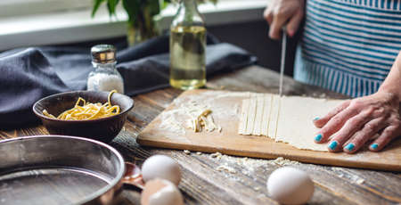 A woman is cutting raw dough with a knife to make homemade noodles. Concept of process of cooking handmade pasta in a cozy atmosphere