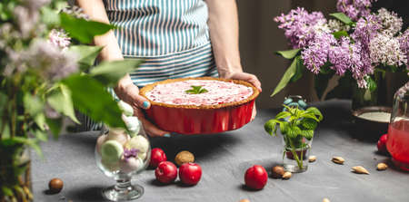 Cooking homemade cranberry pie. A female pastry chef is holding a ready-made lingonberry tart with white sour cream. Table with bright ingredients in spring style with flowers