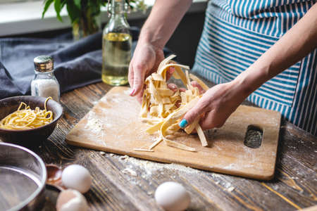 Woman is carefully holding raw fresh homemade noodles in her hands. Concept of process of cooking handmade pasta in a cozy atmosphere