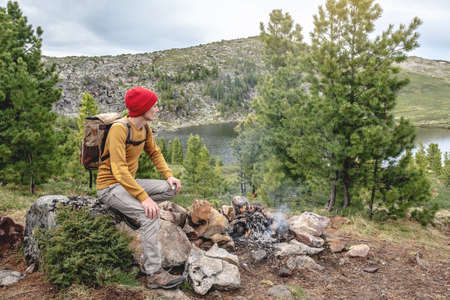 A tourist traveler with a backpack and a red hat is sitting by the campfire and is looking at a mountain lake. The concept of freedom and unity with nature