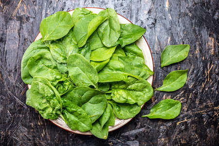 Green leaves of fresh spinach in a plate on a dark background. Healthy vegetarian food. The view from the top.