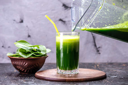 Cooking a vegetarian smoothie from green leaves of fresh spinach. Popular detox drink for healthy eating