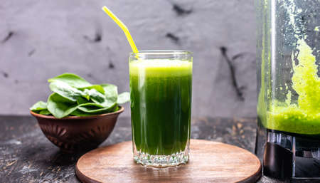 Glass with a vegetarian smoothie made from green leaves of fresh spinach. Popular detox drink for healthy eating