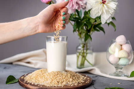 A hand is pouring rice grains into a glass of natural rice milk on the table. Alternative vegetarian drink for a healthy diet