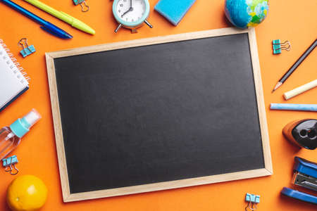 Stationery school supplies around the board on a orange background. Copy space. Concept of back to school.