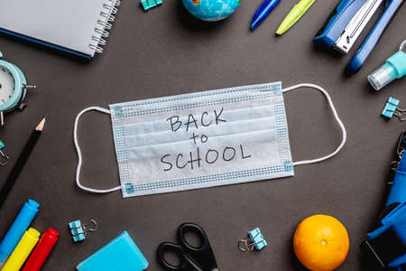 Stationery school supplies around the medical mask on black background. Top view. Concept of back to school.