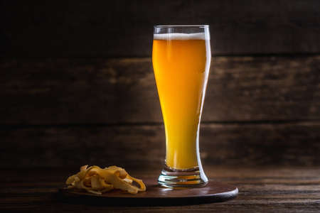 A glass of wheat light unfiltered beer with foam on the table on a dark wooden background Stok Fotoğraf