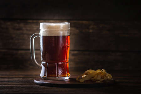 A glass of wheat dark beer with foam on the table on wooden background
