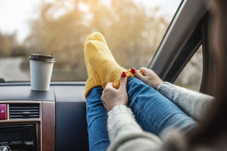 Woman in a car in warm woolen yellow socks on the car dashboard. Cozy autumn weekend trip. The concept of freedom of travel