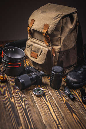Hiking equipment for a tourist on vacation. Backpack, camera, and boots on a wooden table. The concept of an active lifestyle