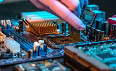 The engineer's gloved hand is holding the CPU chip against the background of the motherboard. Concept of high-tech hardware microelectronics