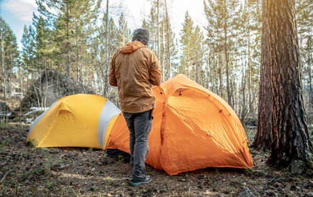 A male traveler is standing in the forest near the tents in a tent camp. Concept of hiking, spending time in nature. Banque d'images