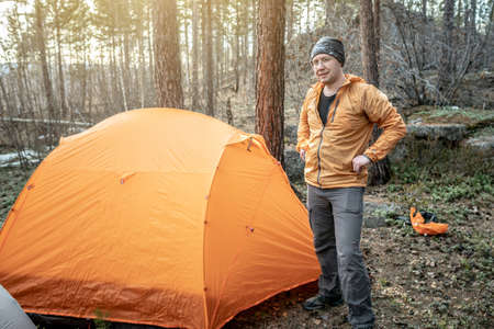 A male hiker is standing in the forest near a tent. Concept of travel, lifestyle, outdoor recreation.