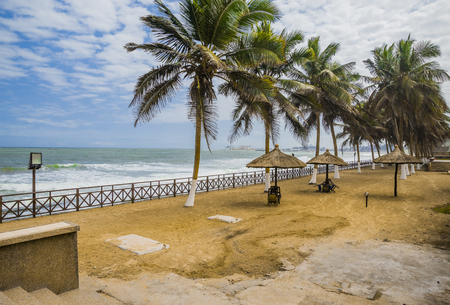 Beach Cafe without visitors. Palm trees, three sunshades and chairs on the sand. Atlantic Ocean and Elmina Castle on a background. Stok Fotoğraf